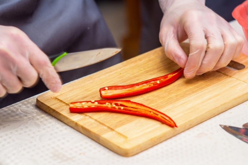 Wearing gloves while chopping peppers helps tremendously when trying to prevent skin burn